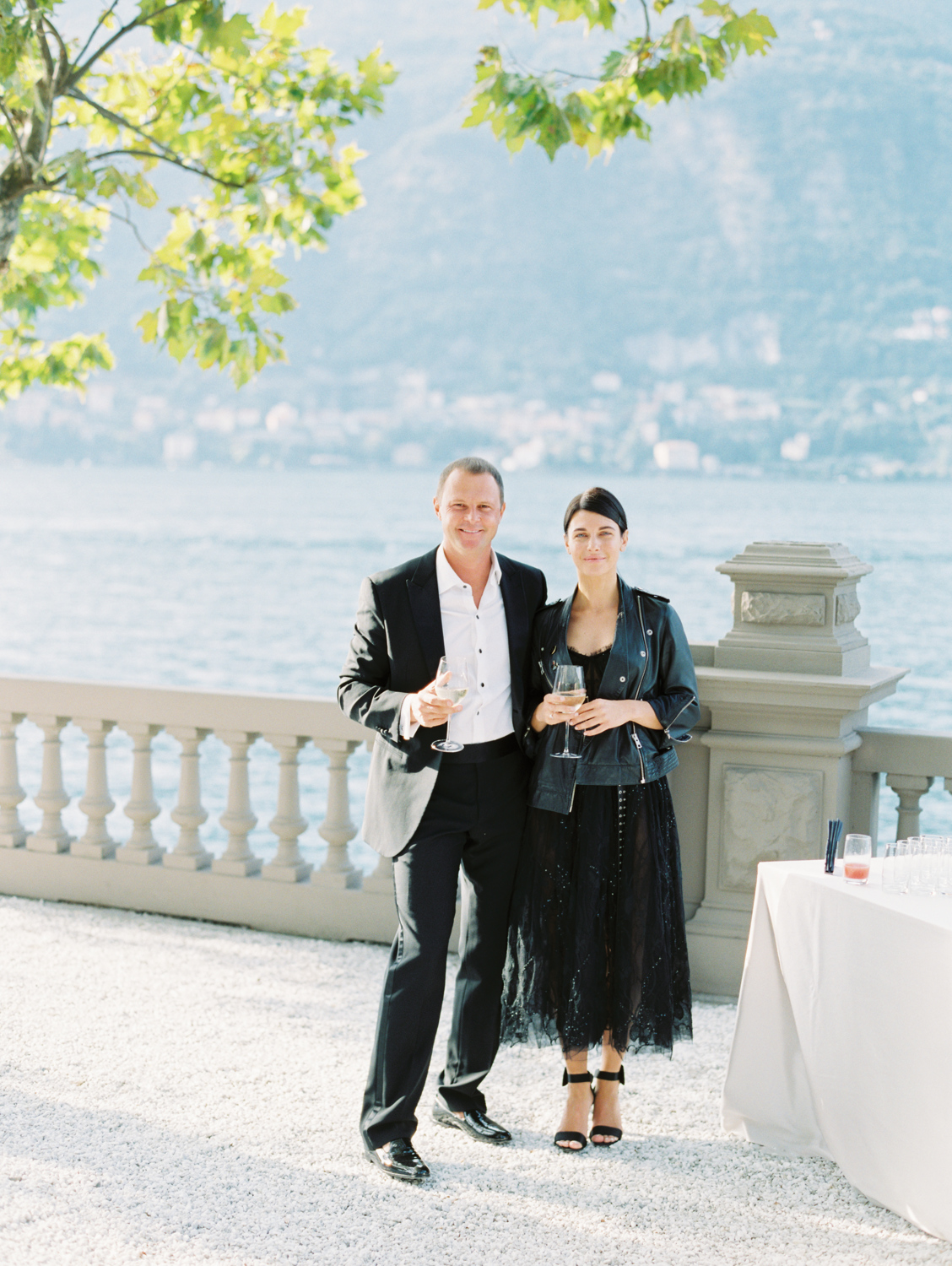Smiling guests with glass of sparkling wine at wedding on lake como