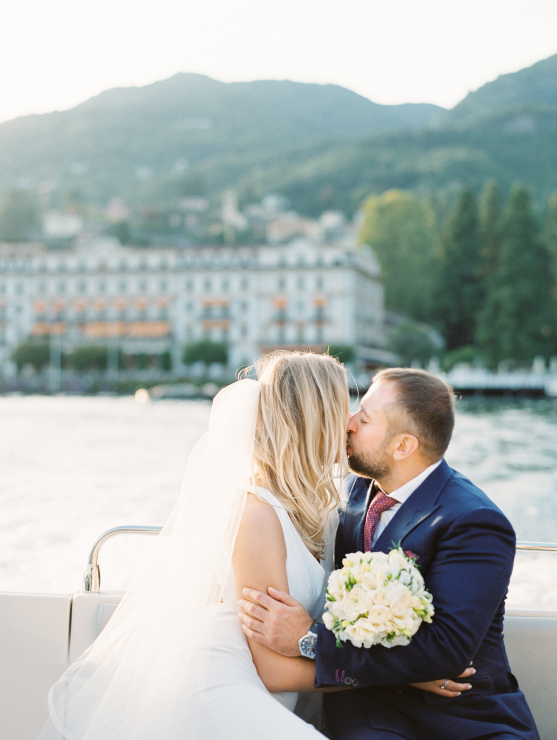 Kissing couple on the boat with beautiful lake como view