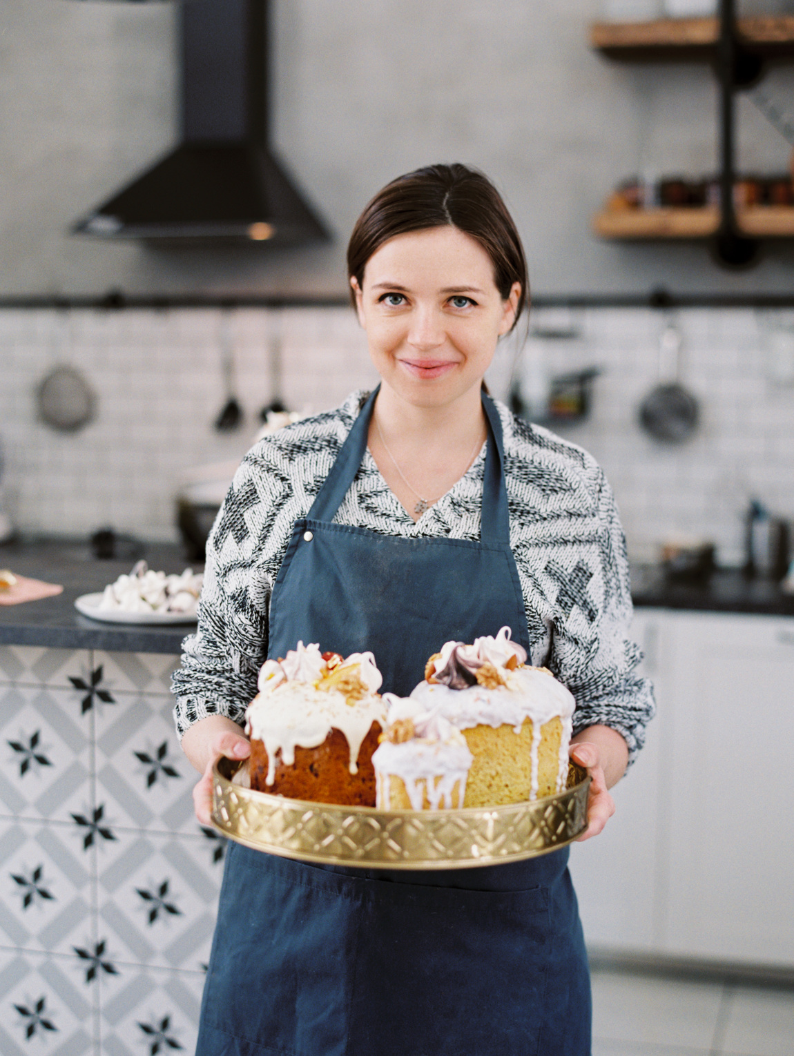 Content woman with tray of holiday cakes
